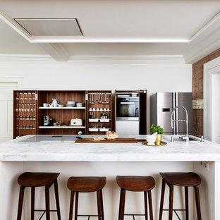 Offene, Einzeilige, Große Moderne Küche mit integriertem Waschbecken, flächenbündigen Schrankfronten, weißen Schränken, Marmor-Arbeitsplatte, Küchengeräten aus Edelstahl, braunem Holzboden, Kücheninsel und braunem Boden in Frankfurt am Main