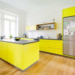 Offene, Zweizeilige Moderne Küche mit Einbauwaschbecken, flächenbündigen Schrankfronten, gelben Schränken, Küchenrückwand in Weiß, Küchengeräten aus Edelstahl, braunem Holzboden, zwei Kücheninseln und braunem Boden in Köln