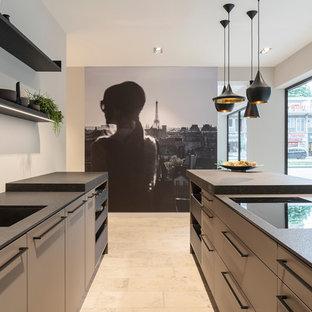 Offene, Zweizeilige, Mittelgroße Moderne Küche mit flächenbündigen Schrankfronten, grauen Schränken, Mineralwerkstoff-Arbeitsplatte, schwarzen Elektrogeräten, Marmorboden, Kücheninsel, beigem Boden, schwarzer Arbeitsplatte, Unterbauwaschbecken und Küchenrückwand in Weiß in Köln