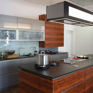 Large contemporary kitchen remodeling - Large trendy dark wood floor kitchen photo in Munich with glass-front cabinets, gray cabinets, gray backsplash, glass sheet backsplash, an island and stainless steel appliances