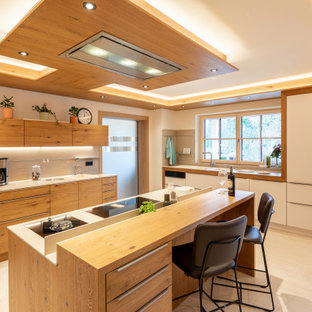 Große Asiatische Küchenbar in L-Form mit flächenbündigen Schrankfronten, hellen Holzschränken, Küchenrückwand in Grau, Küchengeräten aus Edelstahl, Kücheninsel, beigem Boden und weißer Arbeitsplatte