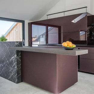 Exemple d'une très grande cuisine américaine parallèle tendance avec un évier 1 bac, un placard à porte vitrée, des portes de placard violettes, un plan de travail en verre, une crédence en feuille de verre, un électroménager noir, béton au sol, un îlot central, un sol gris et un plan de travail violet.