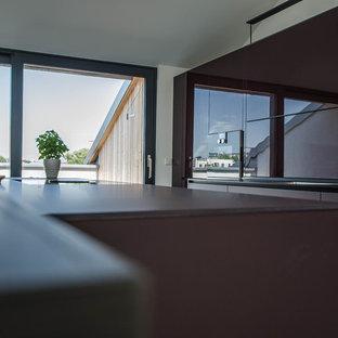 Пример оригинального дизайна: огромная параллельная кухня в современном стиле с обеденным столом, одинарной раковиной, стеклянными фасадами, фиолетовыми фасадами, стеклянной столешницей, фартуком из стекла, черной техникой, бетонным полом, островом, серым полом и фиолетовой столешницей