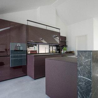 На фото: огромная параллельная кухня в современном стиле с обеденным столом, одинарной раковиной, стеклянными фасадами, фиолетовыми фасадами, стеклянной столешницей, фартуком из стекла, черной техникой, бетонным полом, островом, серым полом и фиолетовой столешницей