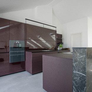 Неиссякаемый источник вдохновения для домашнего уюта: огромная параллельная кухня в современном стиле с обеденным столом, одинарной раковиной, стеклянными фасадами, фиолетовыми фасадами, стеклянной столешницей, фартуком из стекла, черной техникой, бетонным полом, островом, серым полом и фиолетовой столешницей