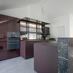 Photo of an expansive contemporary galley eat-in kitchen in Berlin with a single-bowl sink, glass-front cabinets, purple cabinets, glass benchtops, glass sheet splashback, black appliances, concrete floors, with island, grey floor and purple benchtop.
