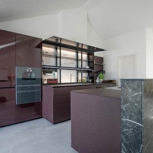 Modern inredning av ett mycket stort lila lila kök, med en enkel diskho, luckor med glaspanel, lila skåp, bänkskiva i glas, glaspanel som stänkskydd, svarta vitvaror, betonggolv, en köksö och grått golv
