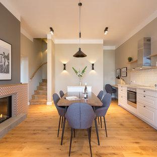 Einzeilige, Große Moderne Wohnküche mit weißen Schränken, Laminat-Arbeitsplatte, Küchenrückwand in Weiß, Rückwand aus Metrofliesen, Küchengeräten aus Edelstahl, weißer Arbeitsplatte, braunem Boden und braunem Holzboden in Berlin