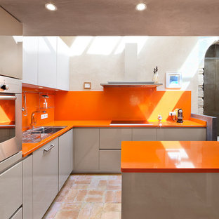 This is an example of a large contemporary l-shaped eat-in kitchen in Stuttgart with a drop-in sink, flat-panel cabinets, grey cabinets, orange splashback, stainless steel appliances, with island, terra-cotta floors and orange benchtop.
