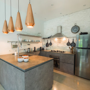 This is an example of a small mediterranean u-shaped open plan kitchen with a drop-in sink, flat-panel cabinets, grey cabinets, marble benchtops, white splashback, brick splashback, stainless steel appliances, concrete floors, with island, beige floor and grey benchtop.