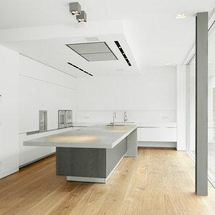 Große Moderne Küche in L-Form mit Kücheninsel, flächenbündigen Schrankfronten, weißen Schränken, Küchenrückwand in Weiß, hellem Holzboden und Betonarbeitsplatte in Hamburg