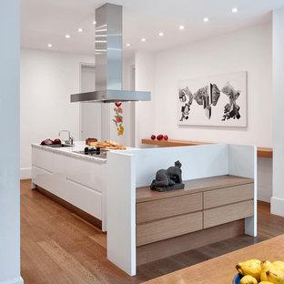 Geräumige, Zweizeilige Moderne Wohnküche mit Einbauwaschbecken, flächenbündigen Schrankfronten, weißen Schränken, Marmor-Arbeitsplatte, Küchenrückwand in Weiß, braunem Holzboden, Kücheninsel, braunem Boden und weißer Arbeitsplatte in Frankfurt am Main