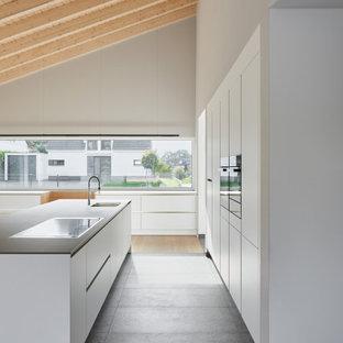 Modelo de cocina comedor lineal, moderna, con fregadero encastrado, armarios con paneles lisos, puertas de armario blancas, encimera de granito, salpicadero blanco, salpicadero de madera, electrodomésticos de acero inoxidable, suelo de terrazo, una isla, suelo gris y encimeras grises