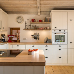 Small country eat-in kitchen in Munich with a farmhouse sink, louvered cabinets, white cabinets, wood benchtops, white appliances, medium hardwood floors, a peninsula, brown floor and brown benchtop.