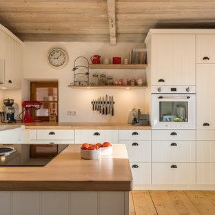 Kleine Landhaus Wohnküche mit Landhausspüle, Lamellenschränken, weißen Schränken, Arbeitsplatte aus Holz, weißen Elektrogeräten, braunem Holzboden, Halbinsel, braunem Boden und brauner Arbeitsplatte in München