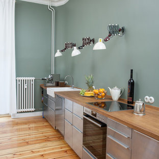 Photo of a mid-sized contemporary single-wall separate kitchen in Berlin with a farmhouse sink, flat-panel cabinets, stainless steel cabinets, wood benchtops, stainless steel appliances, light hardwood floors, no island, beige floor, beige benchtop and green splashback.