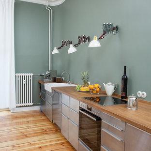 ベルリンの中サイズのコンテンポラリースタイルのおしゃれなキッチン (エプロンフロントシンク、フラットパネル扉のキャビネット、ステンレスキャビネット、木材カウンター、シルバーの調理設備の、淡色無垢フローリング、アイランドなし、ベージュの床、ベージュのキッチンカウンター、緑のキッチンパネル) の写真