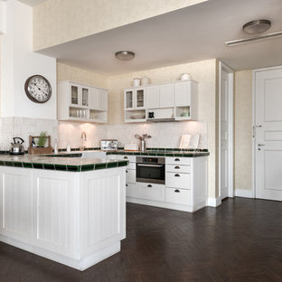 Mid-sized traditional u-shaped eat-in kitchen in Berlin with a drop-in sink, recessed-panel cabinets, white cabinets, white splashback, panelled appliances, carpet, a peninsula, brown floor and multi-coloured benchtop.