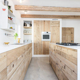 Inspiration for a large industrial galley open plan kitchen in Munich with an undermount sink, flat-panel cabinets, light wood cabinets, solid surface benchtops, concrete floors and with island.