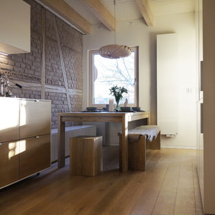 Photo of a large scandinavian single-wall open plan kitchen in Other with a drop-in sink, louvered cabinets, brown cabinets, tile benchtops, grey splashback, glass sheet splashback, black appliances, concrete floors, a peninsula and blue floor.