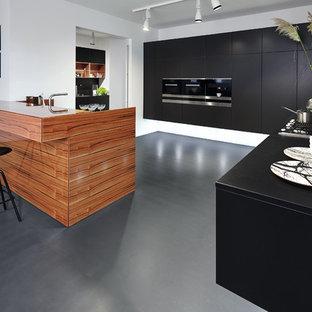 Выдающиеся фото от архитекторов и дизайнеров интерьера: большая п-образная кухня-гостиная в современном стиле с плоскими фасадами, черными фасадами, столешницей из дерева, техникой из нержавеющей стали, полуостровом, накладной раковиной, белым фартуком и полом из линолеума