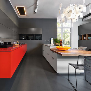 Inspiration for a contemporary eat-in kitchen in Other with flat-panel cabinets, red cabinets, black appliances and a peninsula.