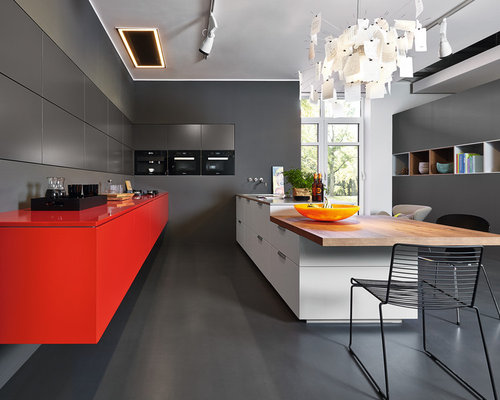Moderne Wohnküche Mit Flächenbündigen Schrankfronten, Roten Schränken,  Schwarzen Elektrogeräten Und Halbinsel In Sonstige