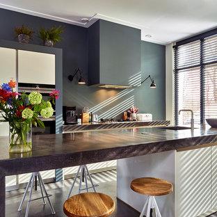 Mittelgroße Moderne Küche mit flächenbündigen Schrankfronten, weißen Schränken, Betonarbeitsplatte, Küchenrückwand in Grau, schwarzen Elektrogeräten, Betonboden, Kücheninsel, grauem Boden, grauer Arbeitsplatte und Waschbecken in Düsseldorf