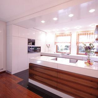 Неиссякаемый источник вдохновения для домашнего уюта: параллельная кухня-гостиная среднего размера в современном стиле с накладной раковиной, плоскими фасадами, темными деревянными фасадами, стеклянной столешницей, белым фартуком, техникой из нержавеющей стали, полом из керамогранита, полуостровом, черным полом и белой столешницей