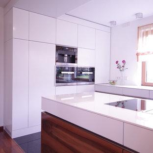 Idéer för att renovera ett stort funkis vit vitt kök, med en nedsänkt diskho, släta luckor, vita skåp, bänkskiva i koppar, vitt stänkskydd, rostfria vitvaror, klinkergolv i porslin, en köksö och svart golv
