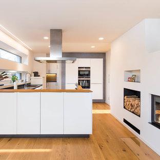 Moderne Küche in U-Form mit Unterbauwaschbecken, flächenbündigen Schrankfronten, weißen Schränken, Arbeitsplatte aus Holz, schwarzen Elektrogeräten, braunem Holzboden, Halbinsel, braunem Boden und brauner Arbeitsplatte in Nürnberg