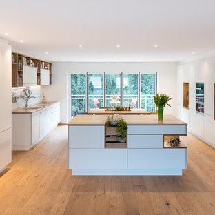 Design ideas for a large scandinavian galley kitchen/diner in Stuttgart with a double-bowl sink, flat-panel cabinets, white cabinets, wood worktops, white splashback, glass sheet splashback, stainless steel appliances, medium hardwood flooring, multiple islands, brown worktops and turquoise floors.
