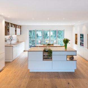 Inredning av ett skandinaviskt stort brun brunt kök, med en dubbel diskho, släta luckor, vita skåp, träbänkskiva, vitt stänkskydd, glaspanel som stänkskydd, rostfria vitvaror, mellanmörkt trägolv, flera köksöar och turkost golv
