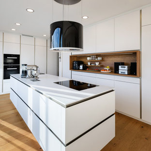 Photo of a mid-sized contemporary l-shaped open plan kitchen in Stuttgart with an integrated sink, flat-panel cabinets, white cabinets, solid surface benchtops, white splashback, timber splashback, black appliances, painted wood floors, with island and brown floor.
