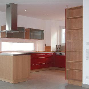 Offene, Geräumige, Zweizeilige Moderne Küche ohne Insel mit Einbauwaschbecken, roten Schränken, Arbeitsplatte aus Holz, grauem Boden, Kassettenfronten und Kalkstein in Frankfurt am Main