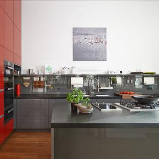 Geschlossene, Große Moderne Küche in L-Form mit Unterbauwaschbecken, flächenbündigen Schrankfronten, Granit-Arbeitsplatte, Küchenrückwand in Schwarz, Glasrückwand, schwarzen Elektrogeräten, braunem Holzboden, Kücheninsel, braunem Boden, schwarzer Arbeitsplatte und grauen Schränken in Dortmund