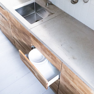 Photo of a mid-sized contemporary single-wall eat-in kitchen in Berlin with an integrated sink, flat-panel cabinets, medium wood cabinets, concrete benchtops, white splashback, ceramic splashback, stainless steel appliances, light hardwood floors and no island.