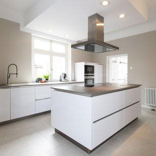 Zweizeilige, Große Moderne Küche mit integriertem Waschbecken, flächenbündigen Schrankfronten, weißen Schränken, Elektrogeräten mit Frontblende, Porzellan-Bodenfliesen, Kücheninsel, grauem Boden und grauer Arbeitsplatte in Sonstige