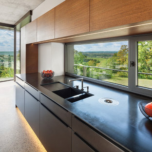 Modern single-wall kitchen in Other with a drop-in sink, flat-panel cabinets, glass sheet splashback, panelled appliances, terrazzo floors and multi-coloured floor.