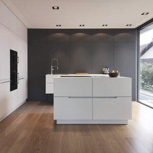 Zweizeilige, Mittelgroße Moderne Küche mit Kücheninsel, Unterbauwaschbecken, flächenbündigen Schrankfronten, grauen Schränken, Elektrogeräten mit Frontblende, braunem Holzboden, braunem Boden und weißer Arbeitsplatte in Sonstige