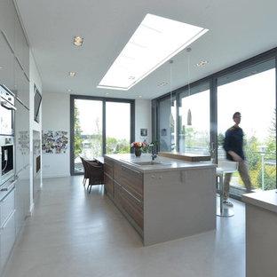 Moderne Küche mit Einbauwaschbecken, flächenbündigen Schrankfronten, grauen Schränken, Küchengeräten aus Edelstahl, Betonboden, zwei Kücheninseln, Küchenrückwand in Weiß und Mineralwerkstoff-Arbeitsplatte in Sonstige
