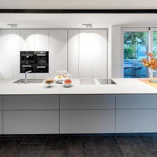 Große Moderne Wohnküche mit flächenbündigen Schrankfronten, weißen Schränken, Kücheninsel, grauer Arbeitsplatte und schwarzem Boden in Stuttgart