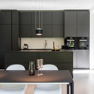 Offene, Mittelgroße, Zweizeilige Moderne Küche mit flächenbündigen Schrankfronten, schwarzen Schränken, Küchenrückwand in Weiß, Kücheninsel, schwarzen Elektrogeräten und weißem Boden in Hamburg