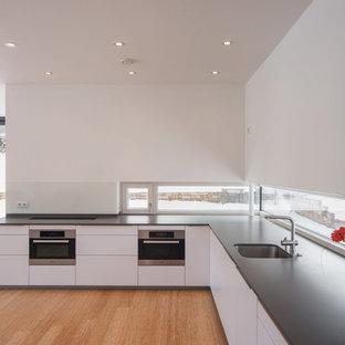 Diseño de cocina en L, moderna, abierta, sin isla, con fregadero bajoencimera, armarios con paneles lisos, puertas de armario blancas, suelo de madera en tonos medios, salpicadero blanco y electrodomésticos con paneles