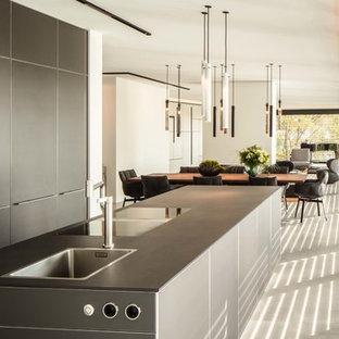 Foto på ett funkis svart kök med öppen planlösning, med släta luckor, svarta skåp, kaklad bänkskiva och en köksö