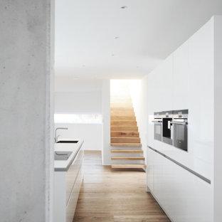 Zweizeilige, Mittelgroße Moderne Küche mit Unterbauwaschbecken, flächenbündigen Schrankfronten, weißen Schränken, Elektrogeräten mit Frontblende, Kücheninsel, beigem Boden und weißer Arbeitsplatte in Bremen