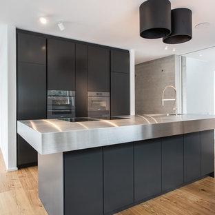 Offene, Zweizeilige, Mittelgroße Moderne Küche mit integriertem Waschbecken, flächenbündigen Schrankfronten, schwarzen Schränken, Edelstahl-Arbeitsplatte, Küchengeräten aus Edelstahl, braunem Holzboden, Kücheninsel, braunem Boden und grauer Arbeitsplatte in Stuttgart