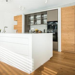 Offene, Zweizeilige, Mittelgroße Moderne Küche mit flächenbündigen Schrankfronten, Küchenrückwand in Grau, schwarzen Elektrogeräten, braunem Holzboden, Kücheninsel, braunem Boden und weißer Arbeitsplatte in Stuttgart