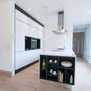 Offene, Große Moderne Küche mit Waschbecken, flächenbündigen Schrankfronten, weißen Schränken, Elektrogeräten mit Frontblende, braunem Holzboden und Kücheninsel in Nürnberg