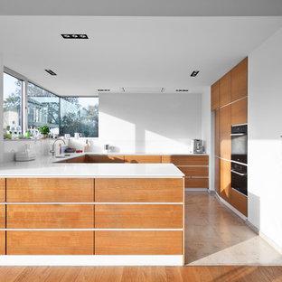 Geschlossene, Große Moderne Küche in U-Form mit flächenbündigen Schrankfronten, hellbraunen Holzschränken, Küchenrückwand in Weiß, Glasrückwand, schwarzen Elektrogeräten, Travertin und Halbinsel in Köln